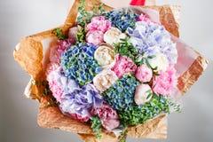 blommasammansättning med vanliga hortensian och pioner Färga rosa färger, gräsplan, lavander, blått kraft papper knaprigt förpack royaltyfria bilder