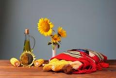 Blommasolrosor i en vas och en etnisk påse Royaltyfria Foton
