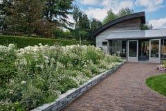 Blommatrottoarkant framme av huset Fotografering för Bildbyråer