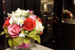 Blommavas på Gray Tabletop med reflexionen och abstrakt suddig Cityscapenattbakgrund som används som mall Arkivbild