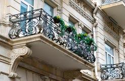 Blommig balkong i en stadsgata Blomkrukor och husv?xter p? balkongen Klassisk stilbalkong med blommor royaltyfri foto