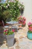 Blommig terrass med trädgårds- möblemang Arkivfoton
