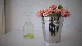 Blommor är i en hink på en vit tabell stock video
