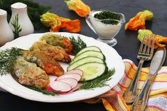 Blommor av zucchinin som lagas mat i smet, skivor av gurkor och r?disor p? en platta royaltyfri foto