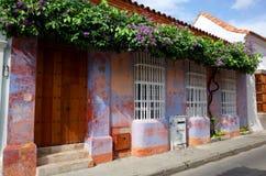 Blommor dekorerar ett purpurfärgat kolonialt hus i Cartagena Royaltyfria Bilder