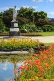 Blommor, det dekorativa dammet och statyn i regeringträdgårdar parkerar, Rotorua, Nya Zeeland royaltyfria foton