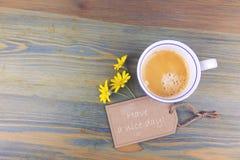 Blommor för kaffekopp och tusenskönamed önskapappetiketten på trätabellen Ha ett romantikermeddelande för trevlig dag Royaltyfria Foton