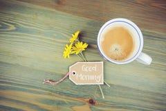 Blommor för kaffekopp och tusenskönamed önskapappetiketten på trätabellen Romantikermeddelande för bra morgon Arkivfoto