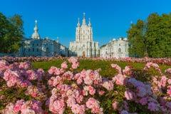 Blommor framme av den Smolny domkyrkan i St Petersburg Arkivbilder