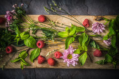 Blommor, hallon och mintkaramell på den bästa sikten för träbräde Royaltyfri Fotografi