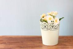 Blommor i blomkruka på trähylla royaltyfri fotografi