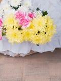 Blommor i den vita korgen på tabellen Royaltyfri Foto