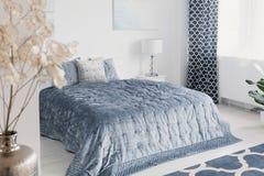 Blommor i det vita eleganta sovrummet som är inre med blåa ark på säng bredvid lampan och förhängear Verkligt foto royaltyfri fotografi