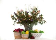 Blommor i en dekorativ vas med frukt Fotografering för Bildbyråer