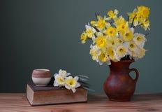 Blommor i en keramisk vas och böcker Arkivfoto
