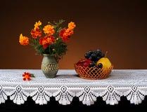 Blommor i en keramisk vas och frukt Royaltyfria Foton