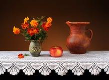 Blommor i en keramisk vas och frukt Royaltyfri Foto