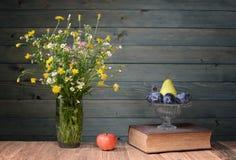 Blommor i en vas gjorde ‹för †av exponeringsglas, böcker och frukt Royaltyfria Bilder