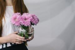 Blommor i en vas i händerna av en flicka En flicka rymmer en vas av blommor blommar vasen Försiktig bröllopbukett i en vas arkivfoto