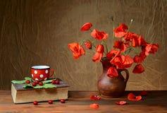 Blommor i en vas med en bok Royaltyfri Foto