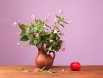 Blommor i en vas och ett rött äpple Royaltyfri Foto