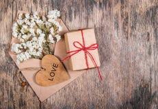 Blommor i ett kuvert, en trähjärta och en ask med gåvan kopiera avstånd Royaltyfria Bilder
