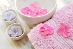Blommor i ett vatten bowlar med en stearinljus och en handduk Royaltyfri Bild