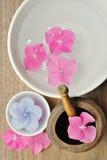Blommor i ett vatten bowlar med en stearinljus och en trämortelstöt Royaltyfri Fotografi