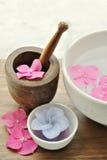 Blommor i ett vatten bowlar med en stearinljus och en trämortelstöt Arkivbilder