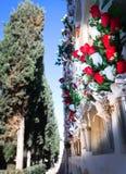 Blommor i kyrkogården nära väggen med jordfästningen Arkivbilder