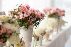 Blommor i rad på en tabell Royaltyfri Bild