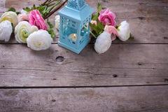 Blommor i rosa färger och stearinljus i blå lykta på tappning w Arkivbilder