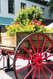 Blommor i vagn över det röda hjulet Arkivfoto