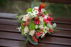 Blommor, lövverk och bär i en runda i en artistisk brud- blom- ordning som vilar på en träbänk med suddig bakgrund Royaltyfria Foton
