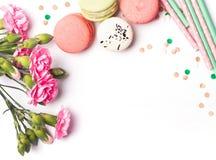 Blommor, macarons och papperssugrör på den vita bakgrunden Fotografering för Bildbyråer