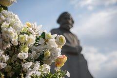 Blommor mot en monument till Karl Marx arkivfoto