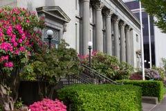 Blommor och blå himmel omger en regeringbyggnad i Washington State royaltyfri bild