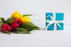 Blommor och en ask med en gåva Begrepp av ferie, födelsedag, Eas Arkivbild