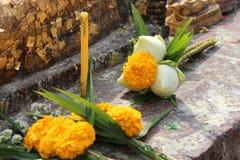 Blommor och en stearinljus sattes som offerings framme av en staty av Buddha i borggården av en tempel (Thailand) Royaltyfria Foton