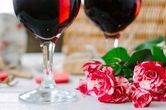 Blommor och exponeringsglas av vin på beröm av valentin dag Royaltyfria Bilder