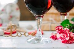 Blommor och exponeringsglas av vin på beröm av valentin dag Royaltyfri Foto