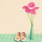 Blommor och flickaktigt skor för rosa färger Arkivfoto