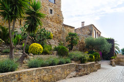Blommor och grönska smyckar gatan av den medeltida staden Arkivbild