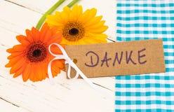 Blommor och hälsningkortet med det tyska ordet, Danke, hjälpmedel tackar dig Arkivbilder