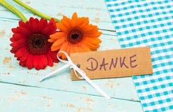 Blommor och kortet med det tyska ordet, Danke, hjälpmedel tackar dig för fader- eller moderdag Arkivfoton