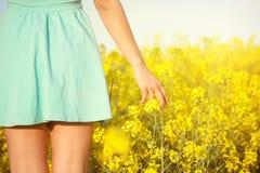 Blommor och kvinnan gömma i handflatan i fältet Arkivfoto