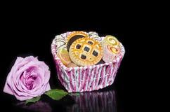 Blommor och sötsaker på en svart bakgrund med reflexion Royaltyfri Bild