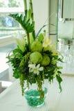 Blommor och sidor i en glass vas Arkivbild
