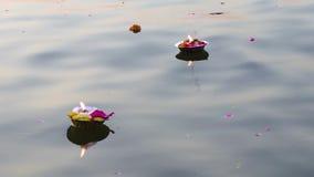 Blommor och stearinljus för puja för religiös ceremoni för Hinduism på det sakrala flodGanges vattnet i Varanasi, Indien, slut up stock video
