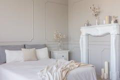 Blommor på den vita tränightstandtabellen i lyxig sovruminre med konungformatsäng fotografering för bildbyråer